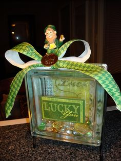 """Lucky You""  -  I had to make me a new St. Patrick's Day table decoration for my office since someone else needed the first one I made.  The leprechaun, glass block, stand and scrapbook paper can be found at Hobby Lobby.  The ribbon, coins, and glass stones came from Michael's...where else is there to shop?!?"