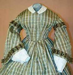 """Civil War Ribbed Silk Dress   c. 1860-1862 United States, PA   Materials Used: Olive green and cream striped silk, velvet and silk fringed ribbon, glazed cotton lining, 5 whalebone stays, brass hooks and eyes (some missing) and wool hem binding.   Condition: Excellent. No holes or wear to the fabric and trim. There is a light brown nickel sized stain on the left side back bodice (just below the shoulder seam) and a very faint underarm stain on the left side.   Measurements: B, 33""""; W, 23""""; Sh-Sh"""