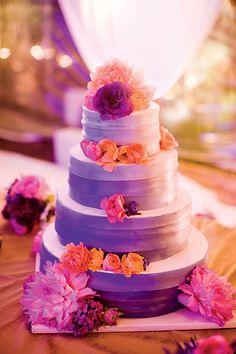 bright purple, lavendar wedding cake with fresh pink flowers and orange roses