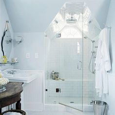 Like the shower inset into dormer with a frameless shower door..Great use of space. Also like the blue color.