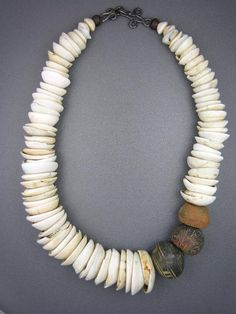by Anne Marie |  Necklace combining antique conus shells used as currency over the centuries in Mauritania, together with three spectacular antique spindle whorls from Mali. Although often collected and strung as beads, whorls were originally used as counterweights to help spin thread. Made of clay and stone and incised with geometrical patterns, they are recognizable by their enlarged central hole. Recent excavations in the old city of Djenne show whorls to have been used at least since 1000AD