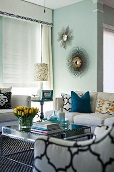 gorgeous blue & green living room design with bold geometric prints, blue gray walls paint color, ivory drapes & cornice box, white & black windsor smith fabric chairs & pillows, square modern, cocktail table, bold blue & yellow floral pillows, wall sunbursts and white sofas.