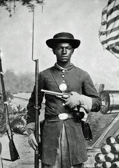 African American soldier in Union uniform with a rifle and revolver posing in front of painted backdrop with American flag and artillery pieces (close up shot).
