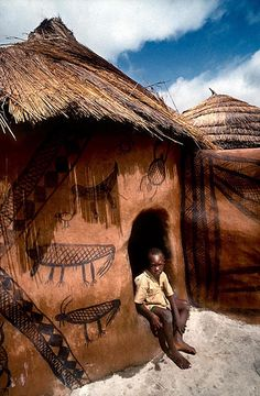 Africa |  A boy sits in the doorway of a traditionally built and painted house in the small town of Zebilla.  Upper East Region of Ghana | © Olivier Blaise