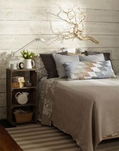 Branching out    Nearly anything can become a headboard, including a pretty branch or piece of driftwood! The wood theme is carried throughout this calming bedroom with a darker wood floor, white-washed boards hung horizontally on the wall, and a nightstand made from a wooden crate. The bedding and accessories are done in beachy earth tones to bring it all together.