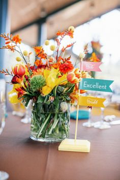 bright floral centerpiece with colorful table signs #tabledecor #weddingflorals #weddingchicks http://bit.ly/1hPiBJl