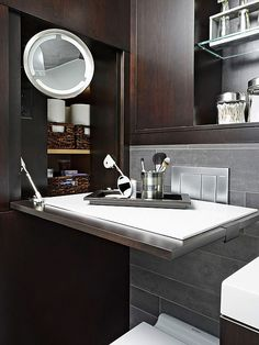 I LOVE THIS>>>Bathrooms that are a tight squeeze, consider a flip-down shelf with hidden storage behind it. The shelf in this tiny bathroom folds out from the wall to be within reach of the vanity. In the wall niche, a makeup mirror turns the shelf into a full-fledged vanity, creating a bathroom that can now accommodate two. As a bonus, the shelf is topped with quartz, a heat-resistant and easy-to-clean surface.