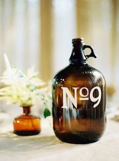 Get into a barn wedding's vibe with glass jug table numbers