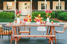 Throw a Retro Backyard Party summer flowers yellow pink and orange   white vases rustic 1960s vintage