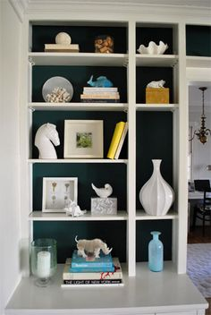 A white bookcase in the corner (maybe Ikea) with either a dark color or a mustard yellow used on the inside.