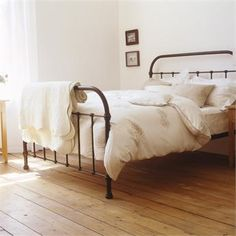 Iron bed and wide pine floors in this simple farmhouse bedroom.