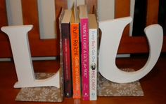 DIY Bookends: Inexpensive homemade bookends. Cover simple plastic or metal L-shaped bookends in attractive paper (the wrapping paper pictured is from the dollar store). Paint wooden letters a complimentary color and glue to the wrapping paper. Ta-Da!    #bookends #DIYBookends