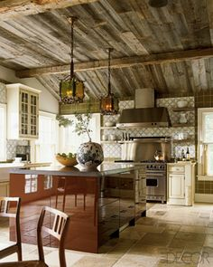 In a kitchen designed by Joe Nahem, a Viking range, GE Monogram hood, and backsplash of 19th-century Portuguese tiles; vintage lanterns hang from a ceiling crafted of antique wood.