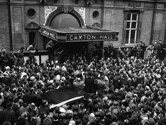 British screen star Elizabeth Taylor and her husband, English actor Michael Wilding stand at the door of London''s Caxton Hall before the huge crowd which massed to greet them after their wedding on the morning of Feb. 21, 1952. (AP Photo)