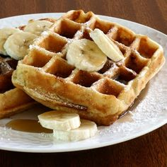 Banana Wheat Waffles with maple syrup and sliced bananas.