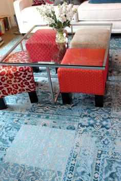 Colorful ottomans under a glass table.