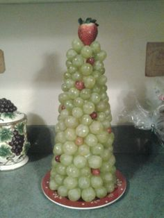 Christmas Grape Tree. Great for parties. Wrap a styrofoam cone with plastic wrap, start at bottom and insert grapes with toothpicks, staggering red ones. Put a plate underneath before finishing for easy manuvering. Strawberry on top or can cut a star from a pineapple.