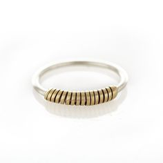 A thin sterling silver ring with brass wrapped around the centre.  Please check our info page for more details on ring sizes.