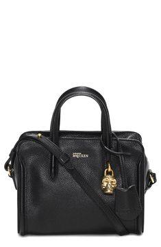 Alexander McQueen leather duffel bag and its signature skull padlock.