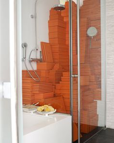 Kevin's beloved collection of Hermes boxes is cleverly stored in the shower and adds a bold kick of color to the bathroom.