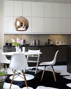 Goyard backsplash, Dixon copper pendant, modern white cabinets, black cowhide