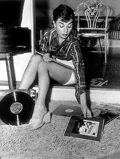 audrey hepburn listening to her record player. black and white photo. music. celebrity. vintage. retro. (original source?)
