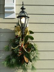 Pine, magnolia leaves gathered and tied with a ribbon for an outdoor light.