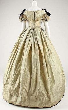 Back view of finely striped evening dress, likely silk, British, ca 1855-60. Pointed bodice, short sleeves, pleated bertha, box pleated skirt.Trimmed with velvet and lace. MET