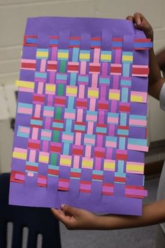 Weaving thin strips over thick strips of paper.