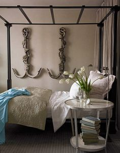 "A curtain in Aubusson in Grey Goose by ClassicCloth forms a ""wall"" behind the four-poster bed, designed by Bobby McAlpine."