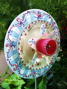 """This flower started with an approx. 12"""" pre-printed plate in a baby blue and white stripe that I adorned with pink, purple and blue decorations. In the center of the flower is a smaller white printed plate with matching polka dots! Finishing off the flower is a white flower shaped tea light holder and then I painted a candle holder pink to match and put a small salt shaker in the very center. All plates are hand painted with a glass paint and baked to set the color in for outdoor use."""