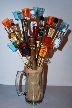 Man bouquet complete with mini booze bottles, shot glasses and cigars! -- I did this as centerpieces for my husband's surprise 30th birthday party. They turned out cute! I used his Alma Mater's plastic drinking cups filled with potting soil and shredded newspapers. I omitted the cigars but used 7 mini bottles and 3 shot glasses per plastic drinking cups.