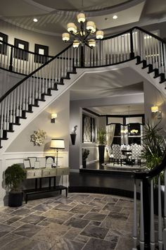 Stunning foyer with twin staircases in black, white, and grey leaning into a dining area in similar colors.