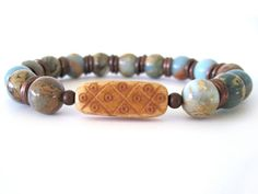 Beautiful beaded stretch bracelet featuring 10mm African opal beads, antiqued copper accent beads and a carved bone focal bead. The opal beads are just gorgeous with hues of blue, rust and tans swirling throughout each stone. This handmade bracelet is quite versatile ... wear individually or stack with other Rock & Hardware bracelets for a more stylish option.