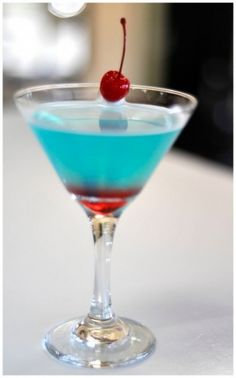 Love Potion Signature Cocktail Grape Vodka, Triple Sec, Blue Curacao, Sweet and Sour Mix, a splash of 7-up, layered grenadine at the bottom of the glass and a cherry garnish