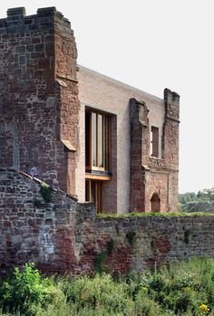 A contemporary house inserted behind the crumbling walls of a ruined twelfth-century castle in Warwickshire, England