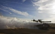 An Israeli tank drives near the border between Israel and the Gaza Strip