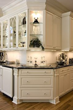 Classic kitchen, white cabinets, white backsplash, dark granite countertops, hardwood floors