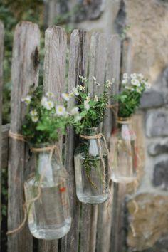 Hand-picked flowers strung in glass milk jars.