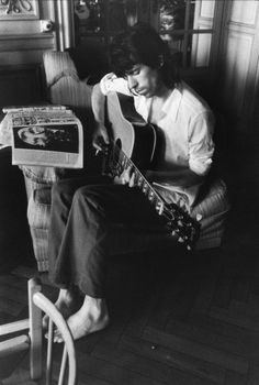 Keith Richards playing guitar and looking at a picture of Brian Jones.