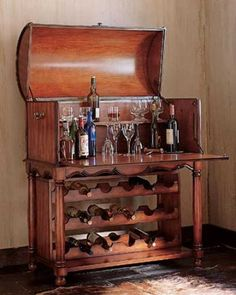 A home bar chest opens to reveal the treasured spirits stocked inside. Lower table has multiple tiered wine racks for bottle storage.