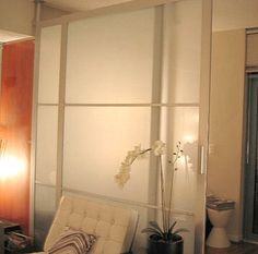 Room divider with sliding closet doors.