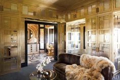 The walls of a dressing room in a Bel Air home designed by Kelly Wearstler are lined with gold-leafed wood paneling inset with antiqued mirrors and trimmed with antiqued brass.