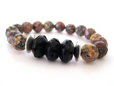 Very cool beaded stretch bracelet featuring 10mm faceted snakeskin jasper beads, hand carved black wood focal beads with pewter accent beads. The color variations in the jasper beads is quite stunning and makes this a truly unique statement bracelet.