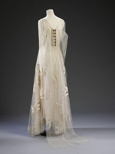 Vionnet Evening Gown. In Vionnet's hands, finishing details such as hems, seams and applied decoration are executed with precision and finesse. This dress was designed by Vionnet in 1935. By this year, Vionnet had operated her own couture house for 23 years and had worked for nearly 50 years in the dressmaking and couture trades. The dress is crafted from organza and fine tulle. Its delicacy is underlined by the scattering of appliquéd velvet swallow motifs across the skirt. cream tull, swallow design, dress, madeleine vionnet, madelein vionnet, evening gowns, tulle, velvet, tull ballgown