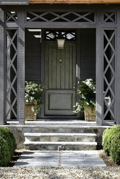 The green door, framed by a charming lattice portico, serves as the perfect complement to the charcoal gray-painted mountain house.