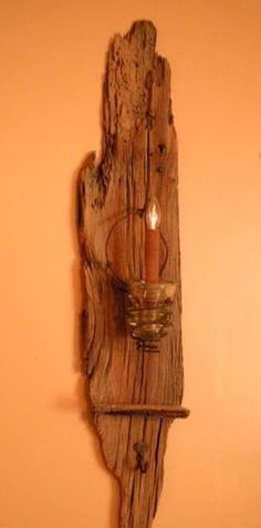 A piece of old barn wood, a bit of wire and one of those old telephone insulators turned upside down!  http://myhoneysplace.com/category/diy-projects/