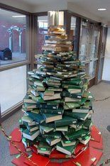 Delta College Librarian Constructs Christmas Tree Out of Books...Librarian Jennean Kabat spent six hours with a couple of coworkers carefully assembling the decoration the day before Thanksgiving...The literary structure — which is buttressed from within by a wastebasket — is comprised of over 100 books. At the bottom, red books were used to simulate a tree skirt. Green books fill out the body of the tree while gold ones round out the top, mimicking a star...The tree is constituted predominan...