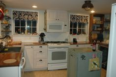 Wood counters, beadboard backsplash, open shelving, plate rack, tilt-out trash bin island.