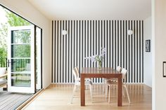 The dining area is set off by a feature wall and NanaWall doors, an accordion design that leads to a cantilevered deck.